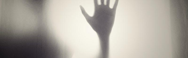 A ghostly shadow is visible behind frosted glass, its hand pressed against the surface in clear relief