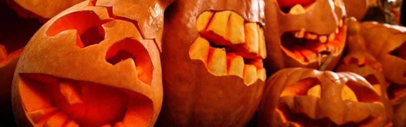 A group of several oddly shaped pumpkins with silly faces carved into them