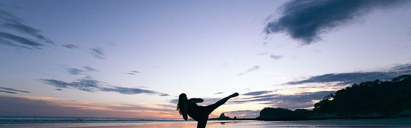 silhouetted woman performs high kick on beach at sunset