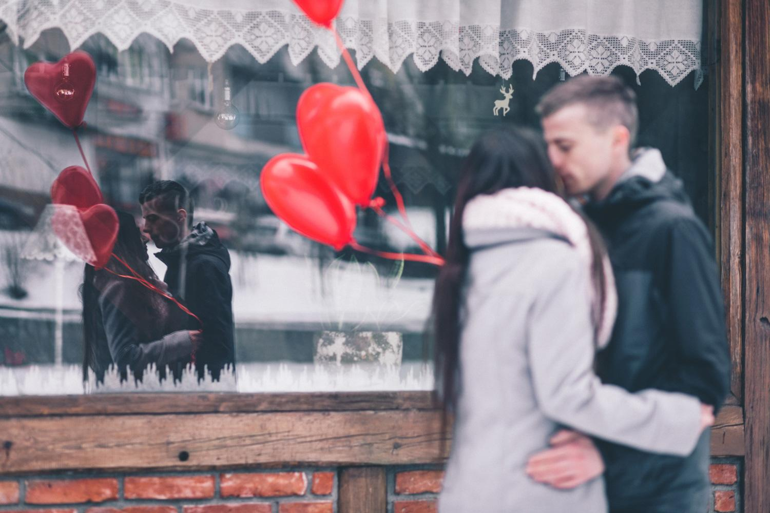 A couple holding red hear balloons kisses outside a shop in winter