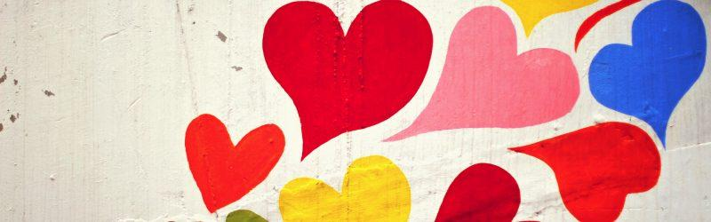 close up of colorful hearts painted on the outside wall of a building