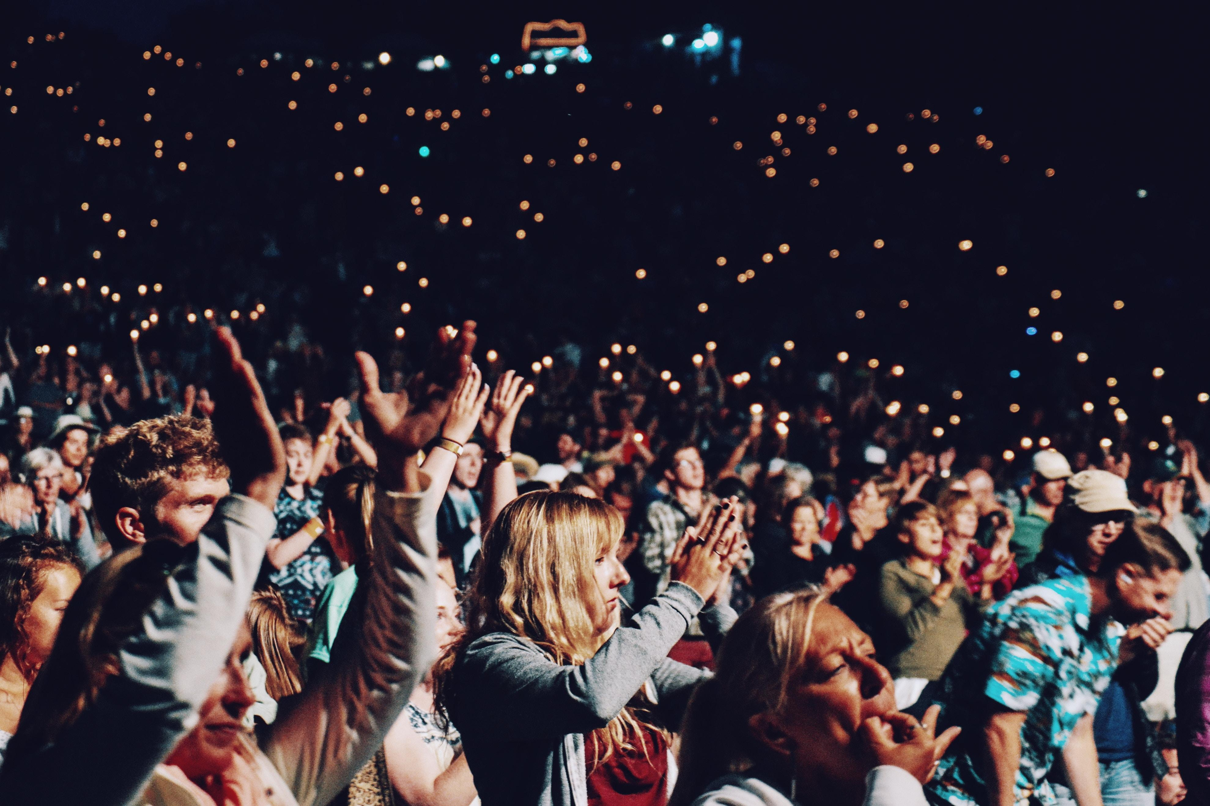 Hundreds of people at a concert at night, lights in the background