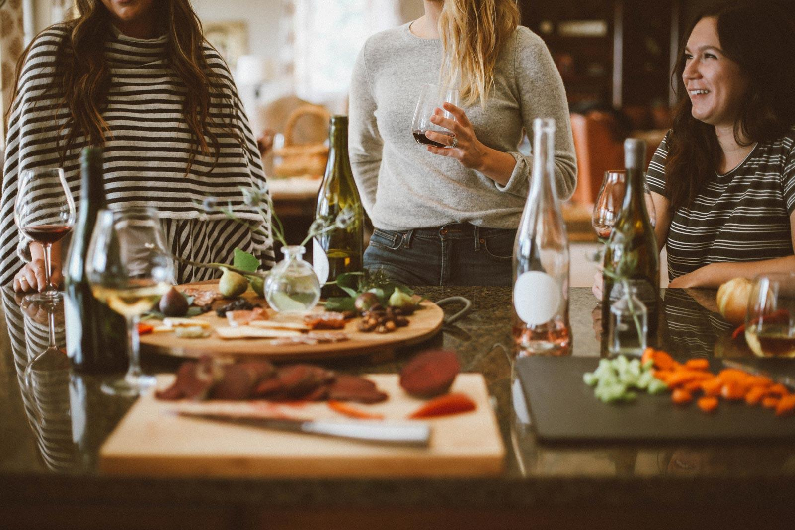Candid shot of three smiling women in conversation, gathered around a table with glasses of wine and charcuterie