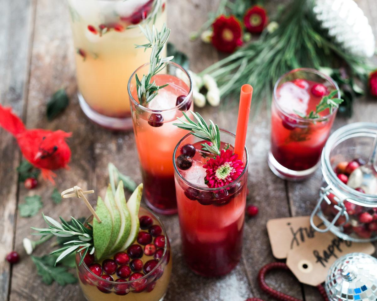 glasses full of bright red drink, berries, and flowers sit on a wood table