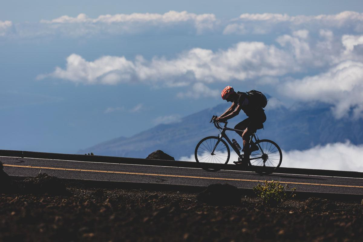 A person rides a bike up a steep road with mountains and clouds in the background