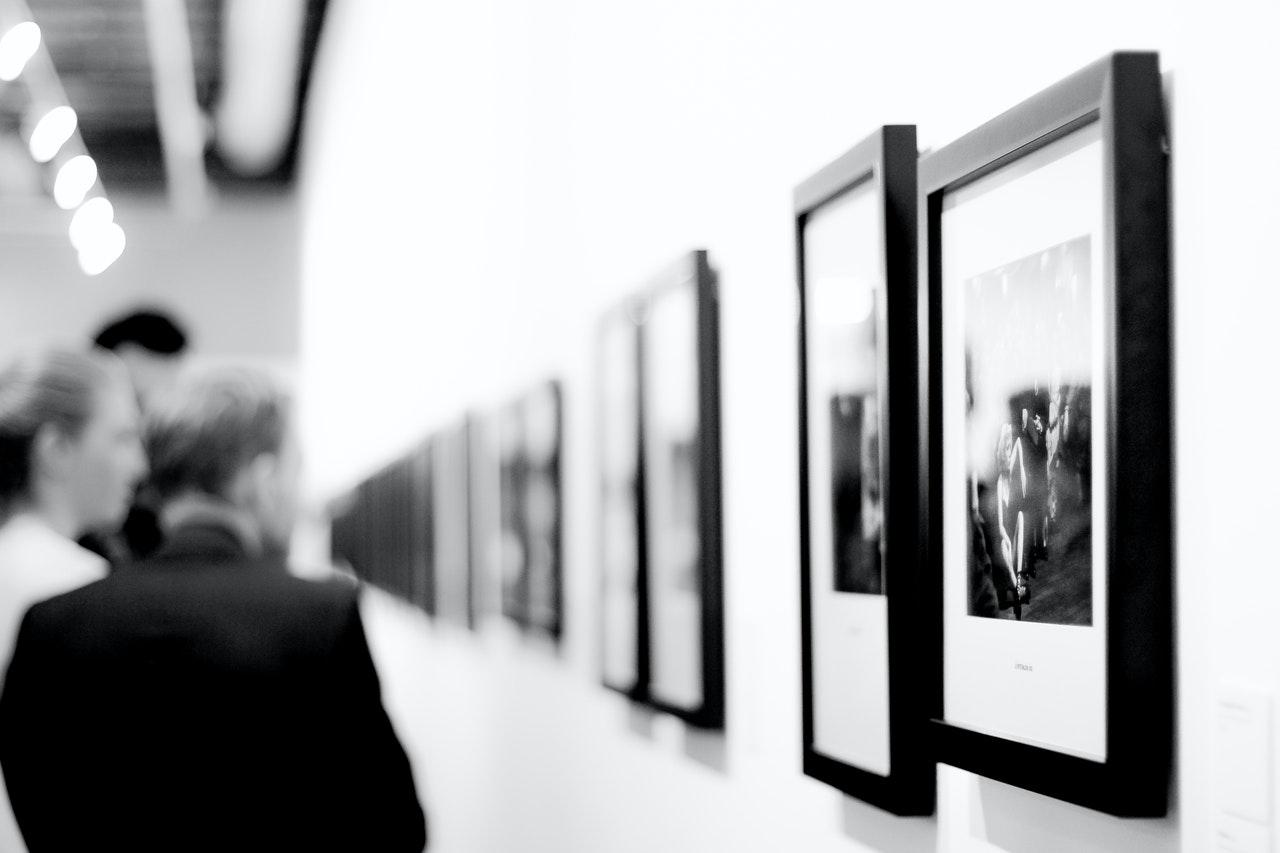 Black and white image of people looking at artwork on wall